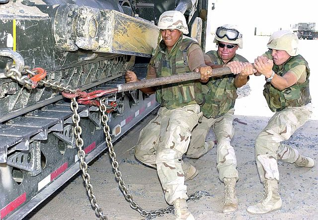 Cheater pipe being used by three military members to close a chain lock on a buldozer transporter.